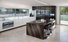 Acrylic cabinets · barstools · black and white · black cabinets · breakfast bar · eat in kitchen · electric cooktop · floral arrangements · kitchen island · minimal · pendant lighting · stone flooring · swivel barstools · tile countertops · waterfall counters · white cabinets · white countertops