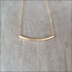 Gold Filled Tube Necklace  A simple 14K gold filled curved tube slides freely on a dainty 14k gold filled chain. This is an essential everyday piece thatll go with just about anything. This necklace looks amazing with other layering necklaces or worn all by itself. I recommend wearing this one in a shorter length with a longer dainty necklace.  ~ 14, 15, 16, 17, 18, 19, or 20 14k gold filled chain ~ 2x30mm (approximatey 1 wide) 14K gold filled tube ~ 14k gold filled spring clasp ~ arrives in…