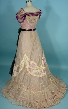 "Circa 1901 G. C. Clark ballgown of embroidered net. The exterior net bodice and skirt have gorgeous ""empiecements"" of lavender floral painted cream colored taffeta."