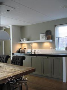 Zwart aanrechtblad, witte spatwand, wanden in dezelfde tint als de keukenfrontjes.