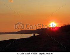 A couple stroll along the beach at sunset.