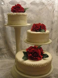3 tier rose cake- separated but together this 3 tier cake is simple beautiful.  Covered with buttercream frosting, with  medium width lace with small gold beads around the bottom of each tier, white buttercream ruffle around the top edge of each tier and large silk roses resting on the top of each tier.  This cake will serve approx, 100 - 125 guest