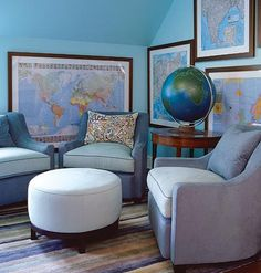 A room with plush blue chairs, a globe, and maps hanging on the walls.