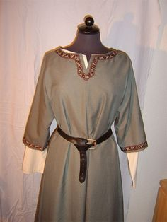 A modern reproduction of an Anglo-Saxon tunic resting on a mannequin. This photo provides a look into the manner of dress for the Anglo-Saxon period - particularly of a base garment worm by members of all socio-economic classes. Through the more earth-based colors, this particular example would most likely belong to an average peasant or freeman.
