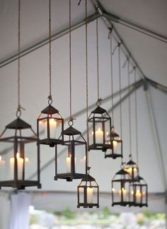 Hang lanterns using twine from the center pole of a tent to use for lighting.