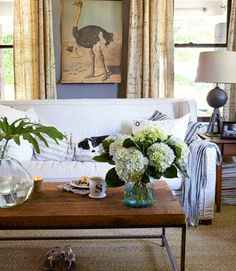"""The neutral palette of this North Carolina house is enlivened by mixing in a variety of textures—the coffee table's reclaimed wood, a nubby sea-grass rug, and a steel lamp base forged from a car jack. Design Legacy linen curtains, printed with an antique script, and striped pillows introduce subtle hints of pattern. """"I wanted a living room that felt calming, not boring,"""" says the owner, an interiors stylist."""