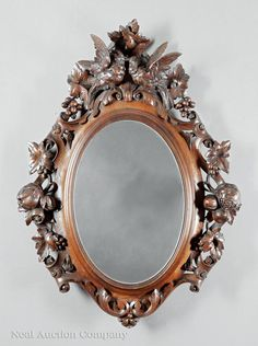 Black Forest Carved Walnut Mirror, 19th c., surround with scrolling foliage surmounted by paired lovebirds, h. 31 in., w. 23 in.
