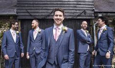 The groom and his groomsmen wear navy suits with dusty pink cravats as they stand outside Upwaltham Barns #upwalthambarns