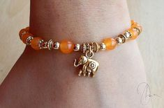 Beaded bracelet with:    ♥ Beautiful orange Quartzite beads  ♥ Tiny antique gold accents  ♥ Small gold dangling elephant charm at the center ♥