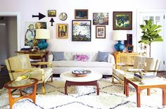 Living room with asymmetrical balance, gallery wall, taupe, purple, gold, black and white, curved shapes
