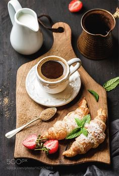 Breakfast set. Freshly baked croissants with strawberry, mint leaves and cup of coffee on wooden board served with pitcher and copper coffee pot over dark woode