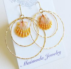 Gorgeous tangerine color sunrise shell beautifully hand wrapped with 14k gold filled wire and suspended from 14k gold filled double hoops. Sunrise shells are about nickel size (3/4 inch) Double eterni