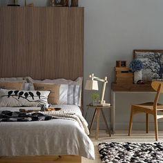 Chambre peinture gris taupe associée à linge de lit couleur lin et mobilier bois doré. Tapis de laine reprenant les couleurs de la chambre