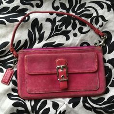 """COACH Pink Suede Slim Wristlet Pre-owned. Front pocket with buckle detail. Lined in brown signature fabric. Magnetic snap button. L 7 3/4"""" H 4.5"""" W 1/4"""". Coach Bags Clutches & Wristlets"""