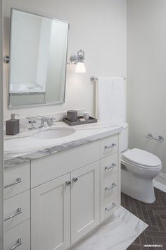 Limestone Herringbone Floors within Calacatta Border, Custom Millwork, Waterworks Plumbing Fixtures at SL3211 Guest Bath.  Designed by Michelle D. Young