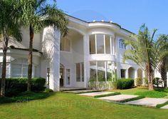 A imponente fachada é marcada pela presença das amplas janelas que revelam os dois pavimentos da residência.