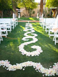 A Patterned Petal Ceremony Aisle  Instead of scattering ceremony aisle petals here and there, ask your florist to arrange them in a fun design like this swirl pattern. (Petal circle designs look cute too!) Word to the wise: Block off the center aisle with ribbon so that guests don't step on your florist's work before the procession.