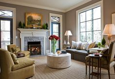 The clean lines and symmetry in this family rooms decor are repeated on the mantel where a silver stag resting on soft greenery is flanked by miniature Christmas trees. A vase of scarlet blooms on the ottoman adds a colorful focal point.