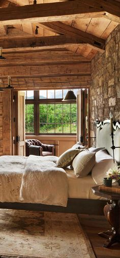 A rustic bedroom with plenty of texture. The combination of wood, metal and stone coordinates perfectly with the olive green curtains and cozy neutral bedding and area rug. Pearson Design Group #loghomes #logcabins #rustichomes #ranchhomes #rusticbedroom #rusticbedroomideas