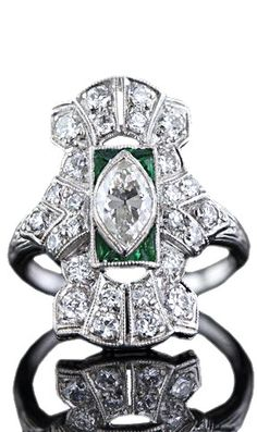 Art Deco Diamond Cocktail Ring.  Or a 'dinner' ring (following the cocktails). A half carat marquise-cut diamond, bezel-set in the center and tipped by calibre-cut emeralds and green glass, forms the heart of this unique sparkler. Twenty-six European-cut diamonds flash and shimmer all up and down the elongated milgrained platinum mount. An original Art Deco treasure from the roaring twenties. Ring size 5 1/2.
