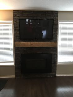 Grey stone with plasma fireplace and 100 year old barn beam mantle