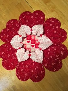 This is a table topper called Heart to Heart. It is created with a shimmering red valentine print, for the larger hearts, and a contrasting white and red heart print for the smaller hearts, which fold open. The folded open hearts are embellished with a felt heart, with a red Rhine-stone, placed at the joining of the hearts. I added a padded center, made from a pink, red, and white heart print, which makes a nice surface for a candle or floral arrangement placement. This table topper…