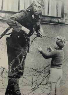 An East German soldier ignores orders to let no one pass and helps a boy, who was found on the opposite side from his family, cross the newl...