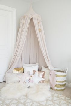 A chic toddler room inspiration! It pairs rose quartz with gold accents and whimsical details like a play tent and a dress-up corner perfect for a little girl's bedroom.