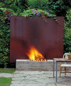 architectural outdoor fireplace with cor-ten steel back guard - houzz via Atticmag  (with stone base)