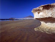 Playa el Médano, Tenerife – Spiaggia attrezzata con sdraio e ombrelloni di sabbia brunita adatta per le famiglie. Grazie al vento costante frequentata anche da windsurfer e surfer.