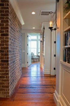 I like the contrast of the brick wall with the abundance of trim work in this hallway.  Except maybe with use stone instead of brick.  I like the bookshelves in a hallway.  I like the old floors.  House of Turquoise: Court Atkins Architects