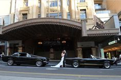 Mustangs in Black 1967 GT Convertible Ford Mustang and 1966 Shelby GT350 Convertible out for Peter and Maria's wedding shoot outside Melbourne's Regent Theatre