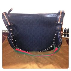 Gucci Black GG Canvas Studded Hobo It is made out of black monogram GG canvas, smooth black leather or the trim and corner panels and golden tone hardware. It's exterior is embellished with detail studs on the strap and bottom corners and Gucci  horsebit decor on each sides of the strap. Gucci Bags Hobos