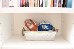 Bookshelf Decor. We are football fans. Signed footballs from family reunions. Add a personal touch to your bookshelves.Master Bedroom DIY Before & After is amazing! See Marlowe-lane.com for more.