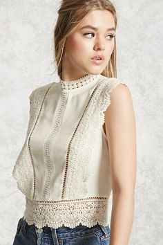 A semi-cropped woven top featuring a crochet trim, a mock neck, ladder cutout inserts, a sleeveless cut, and a button back.