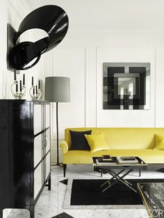 Monochromatic living room with marble tile floors and a yellow sofa