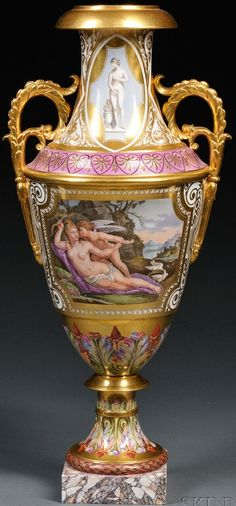 A Paris porcelain~Hand painted and gilded vase~Urn form~Two handled~White ground overlaid with gilded arabesques and strap work~The neck with depictions of classical female nudes~with anthems to the shoulder~The body with two scenes of Venus and Cupid~Over socle with polychrome acanthus leaves and laurel wreath foot~On a square marbleized base Origin France~Circa 1830-1870