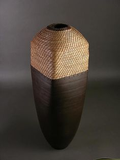 Brown Rectangle by Hannie Goldgewicht. The piece is hand thrown on a potters wheel. After the piece is fired it is finished with patinas and then weaved on the rim with pine needles, and raffia at the end, using the coiling technique.