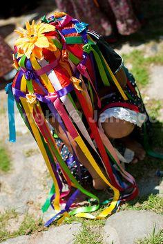 En esta imagen podemos apreciar la combinacion de los elementos naturales como las flores con las cintas de tela de color para formar un diseño de sombrero único. Cada negrita tiene la libertad de confeccionar su sombrero y su vestimenta a su antojo siempre y cuando no se salga del estilo que el disfraz maneja.