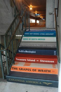 This would even be a cute idea in a residential staircase! I love how the artist painted dimension in the spine of the hardback books. Looks so real.