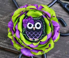 Deluxe Halloween Hootie Tootie Hair Flower Clip or Headband                    $8.95                                 Fun little Hootie Tootie owl dressed in his Halloween colors and perched in a lovely Halloween themed nest.  Flower is a gorgeous and full 4 inch flower done in alternating layers of lime and purple.  It comes mounted onto a partially line alligator clip with non slip