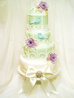 Birdcage cake with large lilac roses, pink cherry blossom and turquoise love birds with painted detail and gold wings.