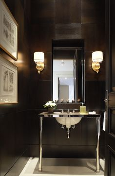 A gorgeous example of a moody masculine-designed powder room -- the wall behind the vanity is made up of leather tile!