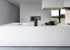 White minimal kitchen - I wonder where those cast iron pots are from An Urban Village: R HOUSE - TAMIZO ARCHITECTS