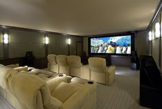 Comfy home theater, picture with all dark gray walls and big comfy chair/couch and projector screen ... Perfection for extra bedroom turned into a home movie room