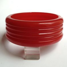 This juicy cherry red Bakelite bangle bracelet is a beauty. Carved in concentric circles with a wider dome at the top and bottom. After carving, it  http://www.rubylane.com/item/414808-3925/Bakelite-Bangle-Bracelet-Carved-Translucent-Cherry