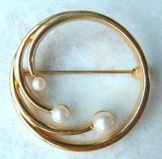 A stunning vintage faux pearl, gold tone circle brooch by Monet.  The brooch is designed in a circular shape with three faux pearls beginning to spiral away from the circle.  The brooch has a secure roll over safety fastening and is signed Monet with the copyright symbol to the back. Circa 1980's