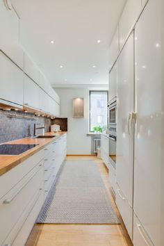 Long and narrow kitchen in white with wooden countertops
