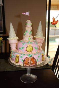 castle cake - fondant icing, buttercream underneath, two round cakes, ice cream cones dipped in pink and white chocolate, also used edible markers