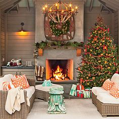 Set a Holiday Scene In Your Outdoor Room | This warm and cozy backyard retreat is decorated for the season. A beautiful Christmas tree takes center stage while the mantle is adorned with fresh greenery. A simple wreath above the fireplace completes the stunning scene.
